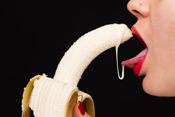 バナナから垂れるものを舐め取る女性